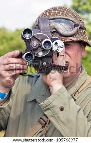 PORTSMOUTH, UK - JUNE 3: A member of the military re-enactment society takes cine footage using a vintage camera of the battle re-enactment at the Overlord Military show on June 3, 2012 at Portsmouth - stock photo