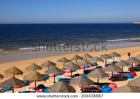 Portugal, Algarve Region, Silves, Arma�§ao de Pera beach with straw sunshades and a crystal clear Atlantic Ocean - stock photo