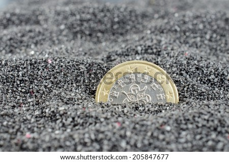Portugal Euro coin sinking in black sand. Euro crisis concept. - stock photo