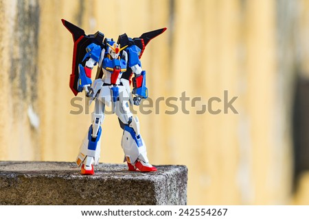 Portugal - January 5, 2015 : Figure of Z-Gundam MSZ-006 from Tamashii Nations & Bandai animations, standing on a rock with a yellow background, in my outdoor garden, Povoa de Lanhoso - stock photo