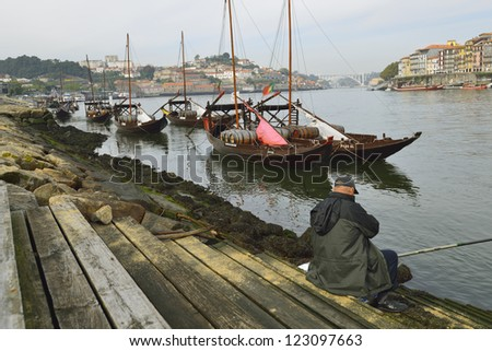 Portugal. Porto, Douro river and old ships and angler - stock photo
