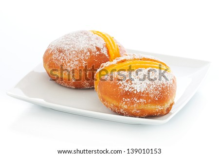 Portuguese doughnut or Berliner with egg creme over a white plate - stock photo