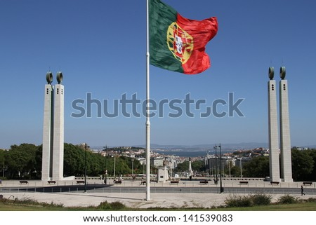 Portuguese flag flying on highpoint with views of Lisbon city - stock photo