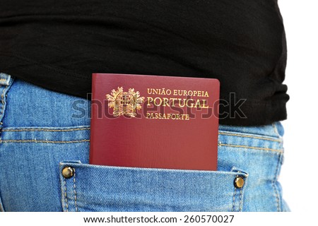 Portuguese passport carried in a rear pocket of jeans pants - stock photo