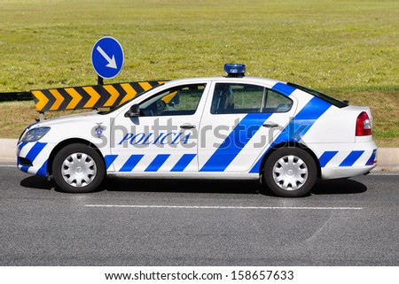 Portuguese police car next to traffic signs and a green field - stock photo