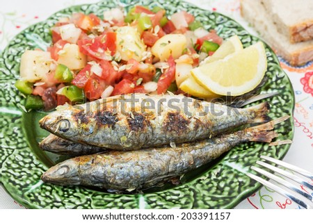Portuguese style grilled sardines with traditional salad - stock photo