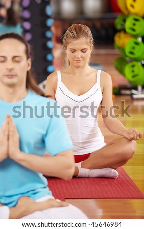 Pose of a lotus performed by two people in sport club - stock photo
