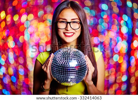 Posh female with toothy smile holding disco ball - stock photo