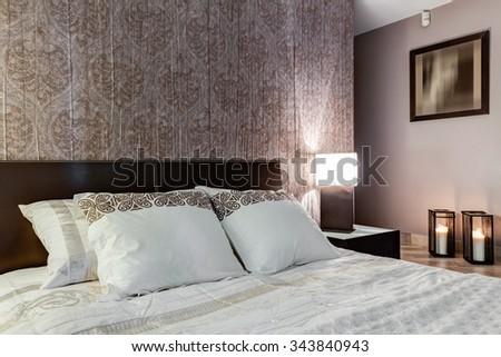 Posh master bedroom with expensive elegant walpaper - stock photo