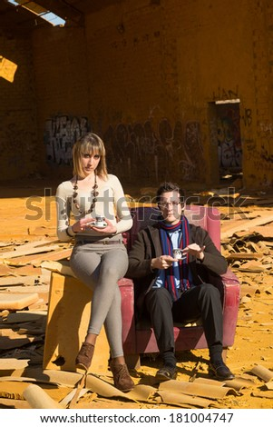 Posh people having tea time among industrial ruins, a concept - stock photo
