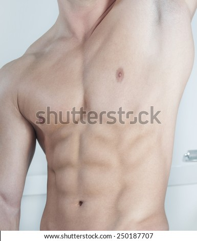 Posing at gym, showing abdominal muscles. - stock photo