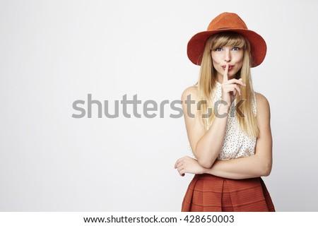 Posing blond woman with a secret, portrait - stock photo