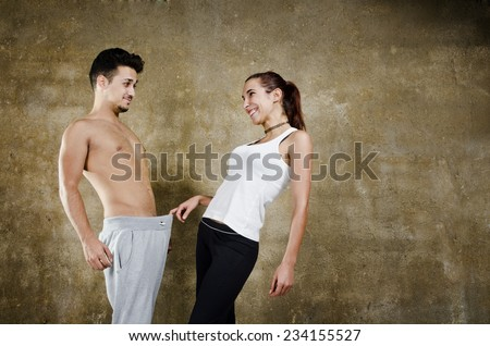 Posing couple in wall background joking about penis and other sexual issues - stock photo