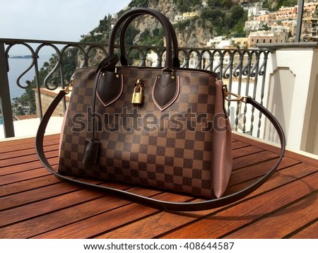 POSITANO, ITALY - APRIL 16, 2016: A Louis Vuitton handbag on a wood table on the balcony of a hotel in Positano, Italy. - stock photo