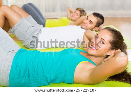 Positive adults at group doing exercises in fitness club. Focus on girl  - stock photo