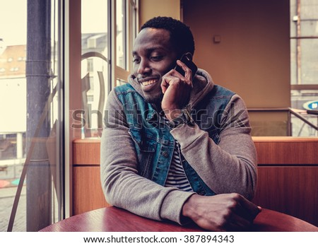 Positive african american man talking on smartphone. - stock photo
