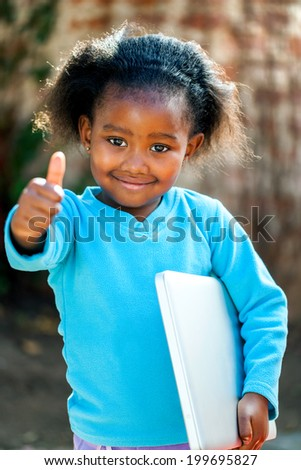 Positive African girl with laptop under arm doing thumbs up. - stock photo