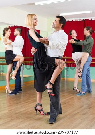 positive american men and women enjoying of tango in class - stock photo