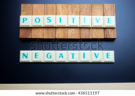 Positive and Negative concept. The words spelled by letters with wood block on blackboard with wooden border. Space for texts. Dark tone. - stock photo