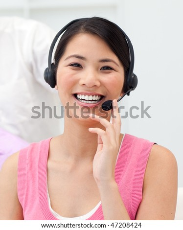 Positive Asian businesswoman talking on headset in the office - stock photo