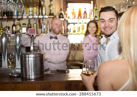 Positive bartender entertaining guests at bar counter  - stock photo