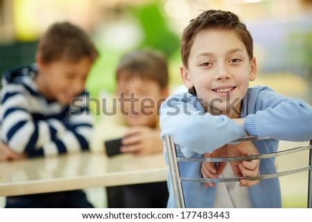 Positive boy sitting in cafe with his friends - stock photo