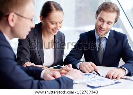 Positive business people analyzing financial aspects of their work - stock photo