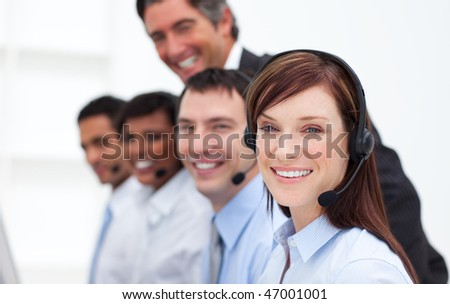 Positive business people working in a call center in a company - stock photo