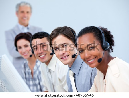 Positive business people working with their manager in a call center - stock photo