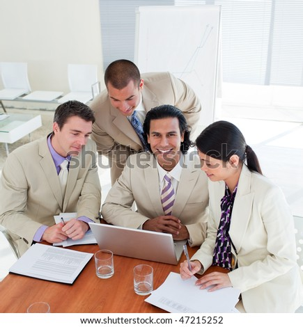 Positive business team working at a computer in a office - stock photo