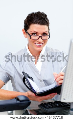 Positive business woman writing on her agenda in the office - stock photo