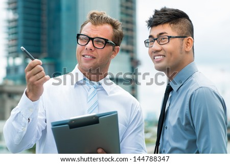 Positive businessmen comparing the project on the screen of a touchpad with an actual building - stock photo