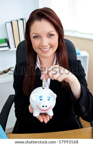 Positive caucasian businesswoman holding piggybank in her office - stock photo
