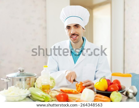 Positive caucasian cook in uniform does vegetables lunch at kitchen - stock photo
