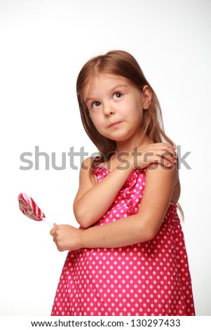 Positive cheerful child holding a red lollipop on Food and Drink - stock photo