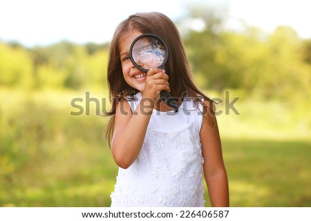 Positive cheerful little girl looking through a magnifying glass outdoors - stock photo