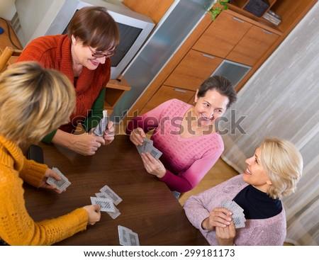 Positive cheerful senior female friends staking money during bridge - stock photo
