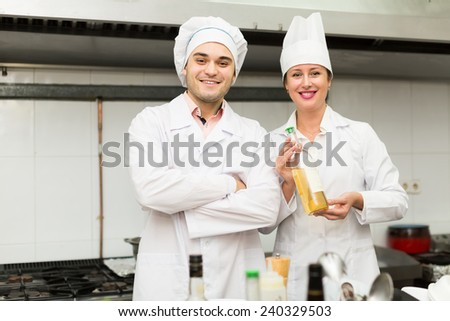 Positive chef and his assistant preparing meal in cafe. Focus on man - stock photo