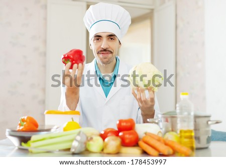 Positive cook man cooking with cauliflower and pepper at kitchen - stock photo