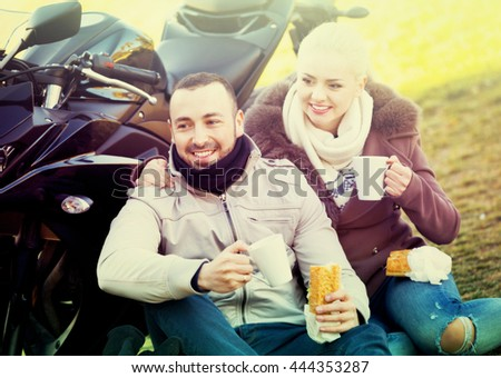 Positive couple having picnic with coffee near cycle - stock photo