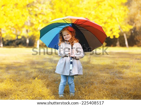 Positive cute child with colorful umbrella in autumn day - stock photo