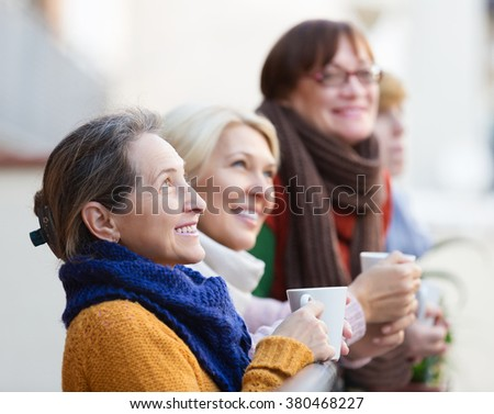 Positive elderly woman in warm clothes having cup of hot tea on terrace. Focus on brunette woman - stock photo