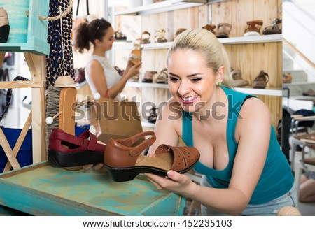 positive european girl holding a picked pair of shoes in the boutique - stock photo