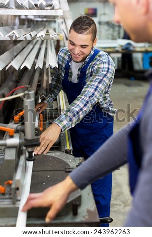 Positive european people working together on a machine in factory - stock photo