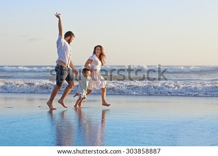 Positive family - father, mother with baby son hold hands and run with fun along edge of sea on smooth sand beach. Active parents and people outdoor activity on tropical summer holidays with children - stock photo