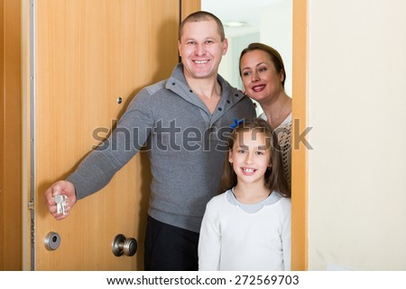 Positive family of three opening door of new apartment  - stock photo