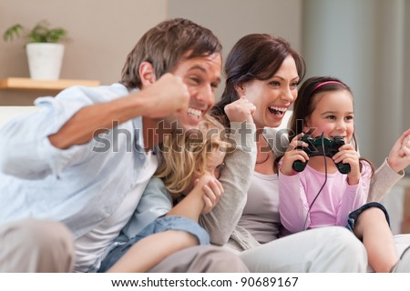 Positive family playing video games together in a living room - stock photo