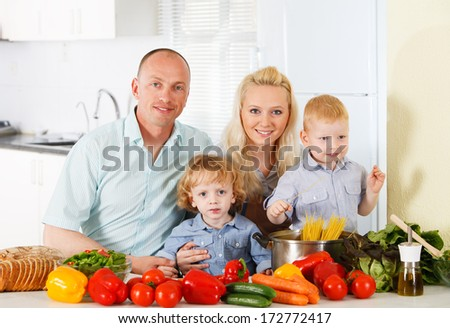 Positive family preparing lunch together  - stock photo