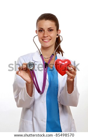 Positive female doctor standing with stethoscope and red heart symbol isolated - stock photo