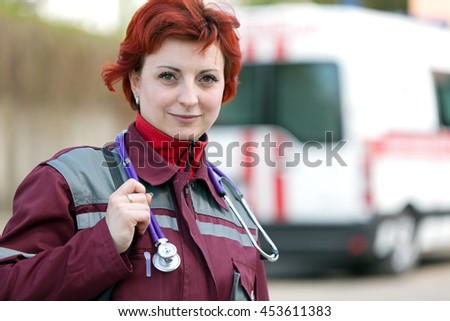 Positive female paramedic with ambulance bag outdoor - stock photo